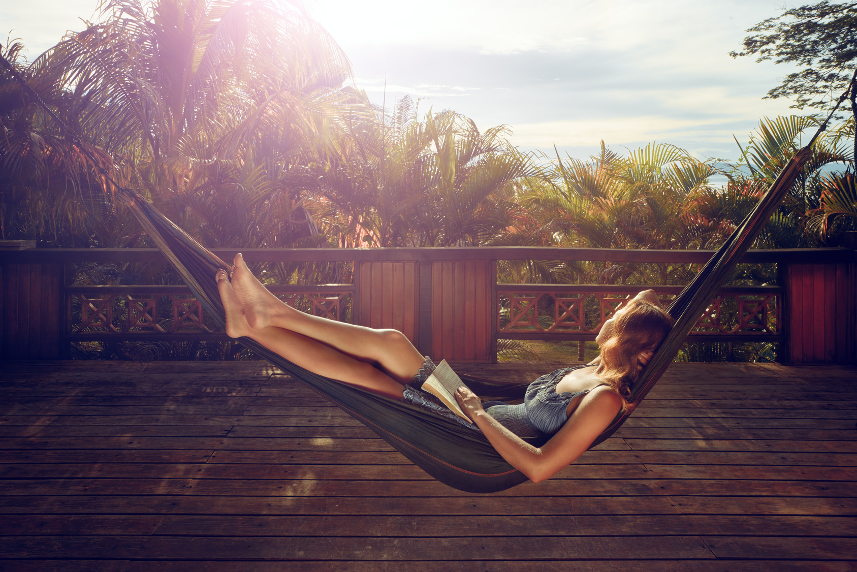woman with book in her hands is resting in ahammock on the terrace against the background of asunset in the jungle during avacation.
